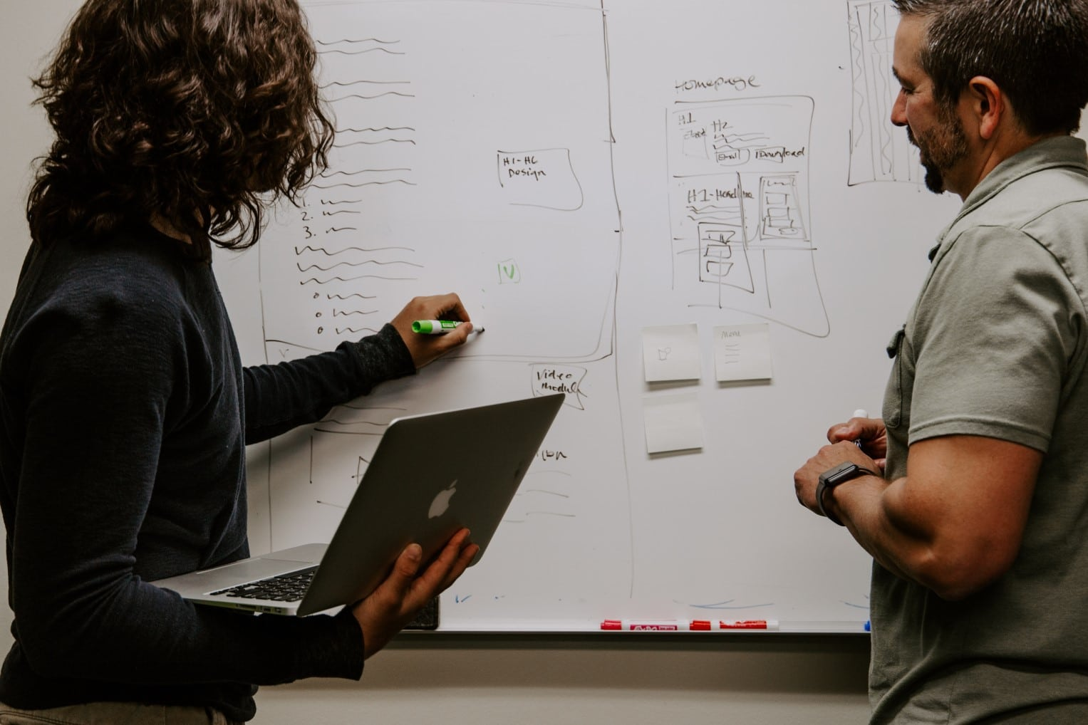 Two people using a whiteboard to plan changes to a website or platform.