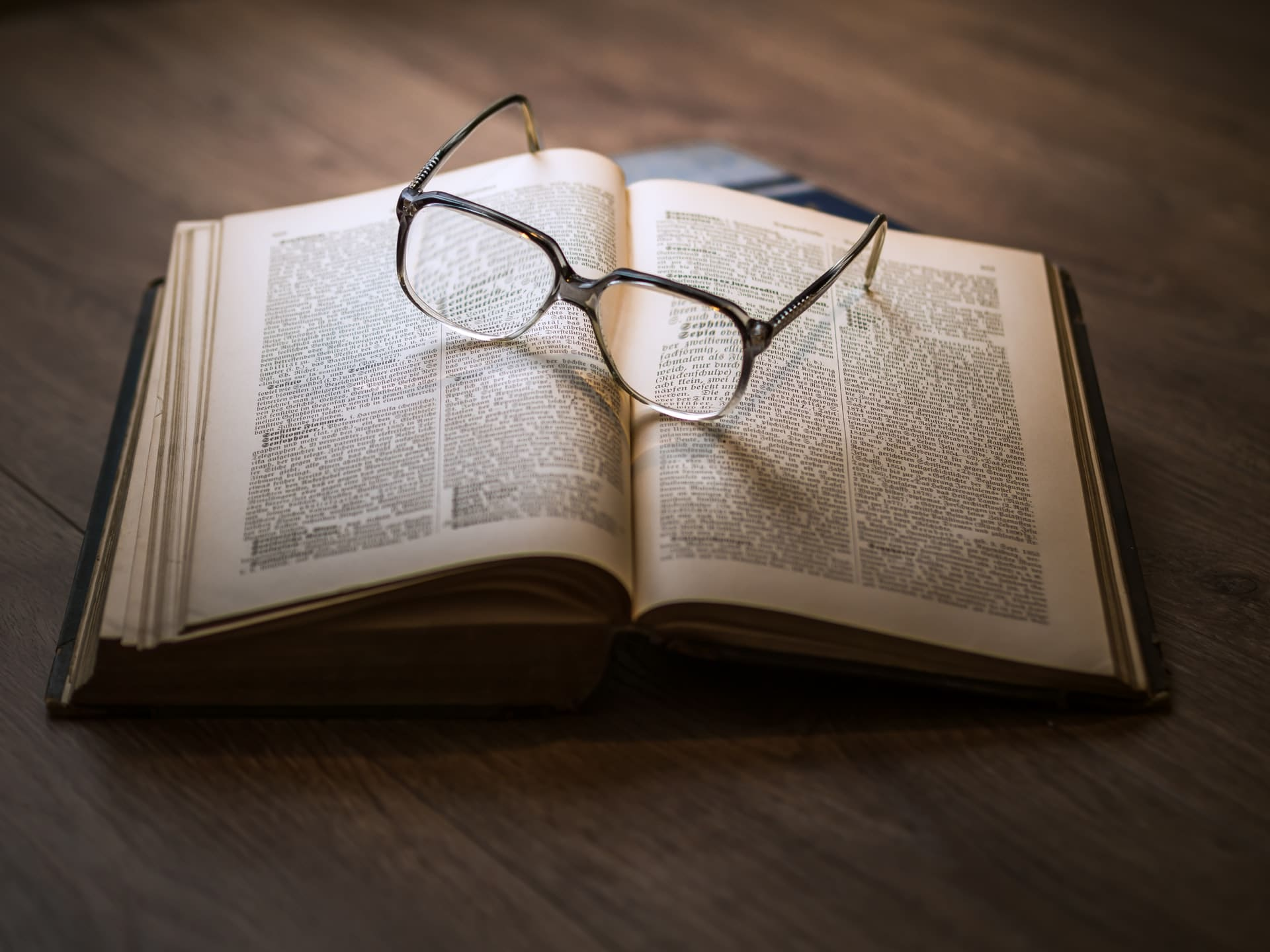Publishing cycle. Text book with glasses.