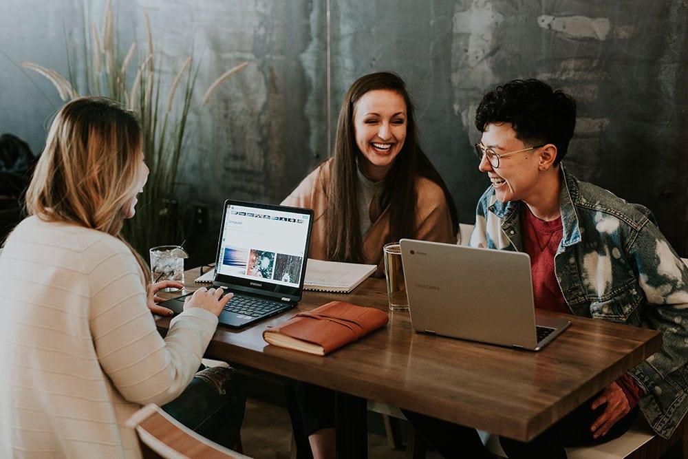 Three students working around laptops