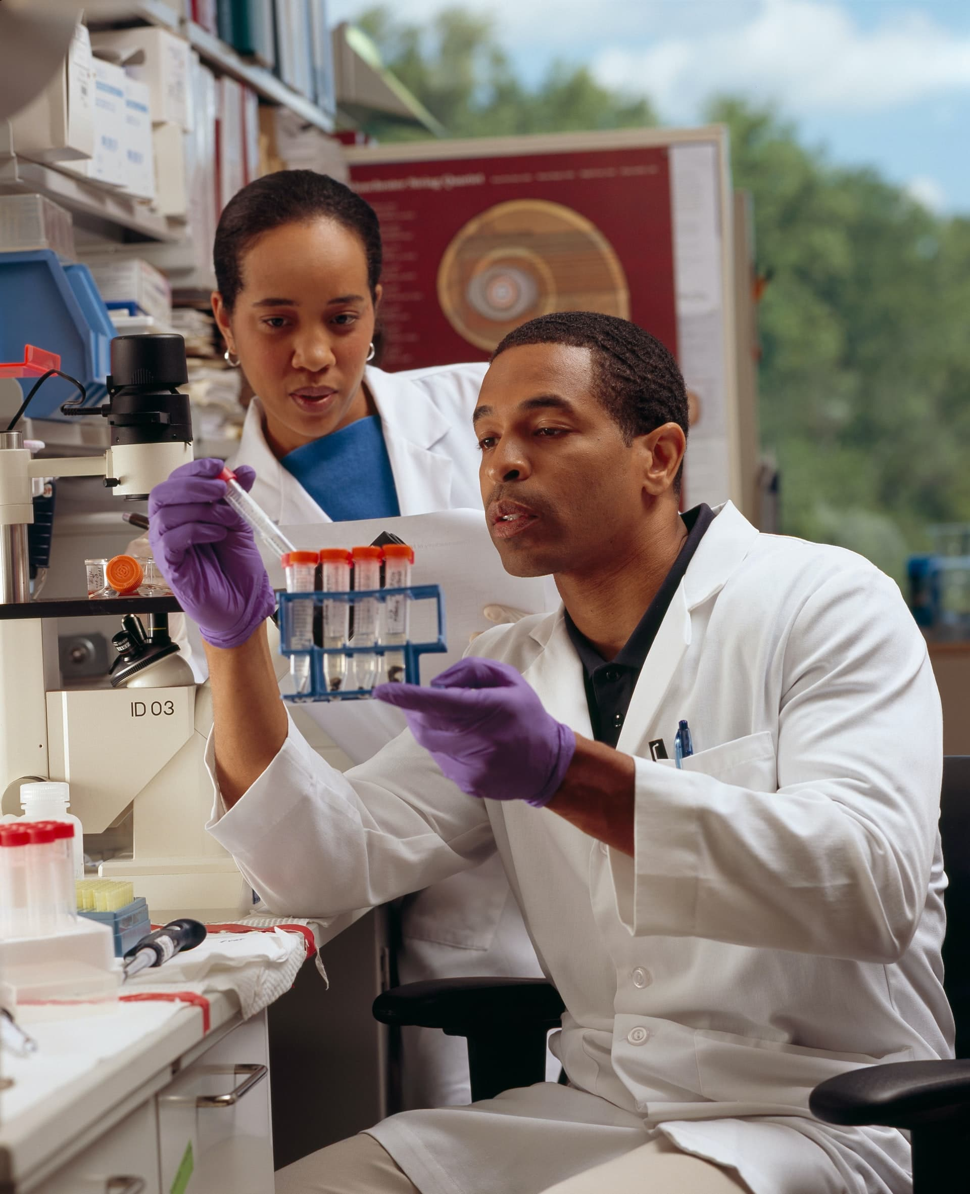 Researcher Checks Test Tubes. An African American male researcher checks test tubes as an AfricanAmerican female cancer researcher looks on.